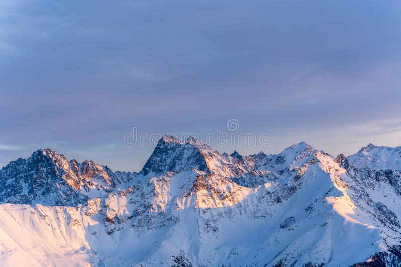 Snowy mountains during sunset in the alps. Glowing snowy mountains during sunset in the alps royalty free stock images