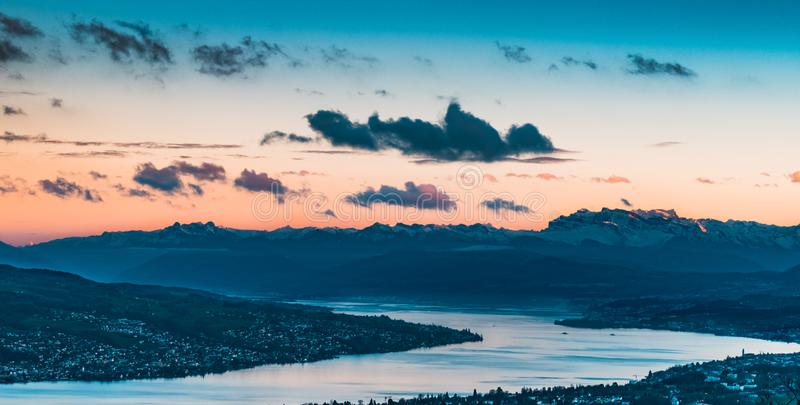 Snowy mountain, sunset and river. Snowy mountains, sunset, clouds and houses around the river stock photo