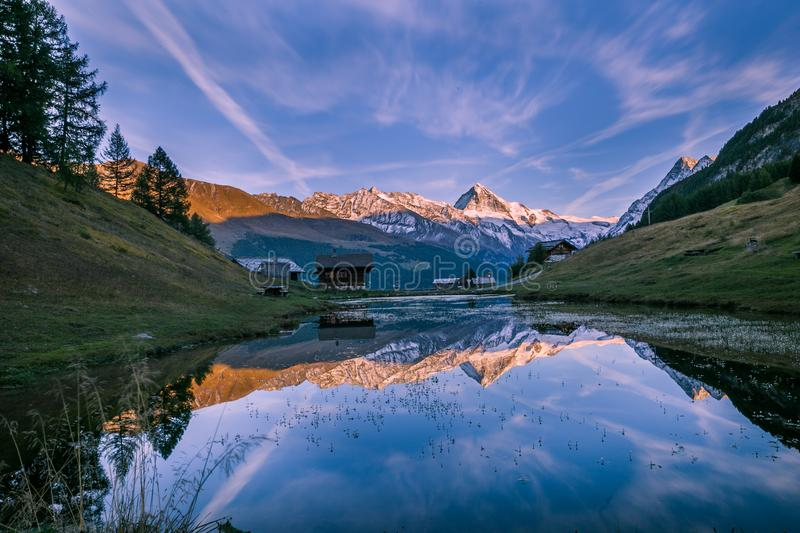 Snowy Mountains and Wood Chalet Reflecting in Altitude Lake at S royalty free stock photos