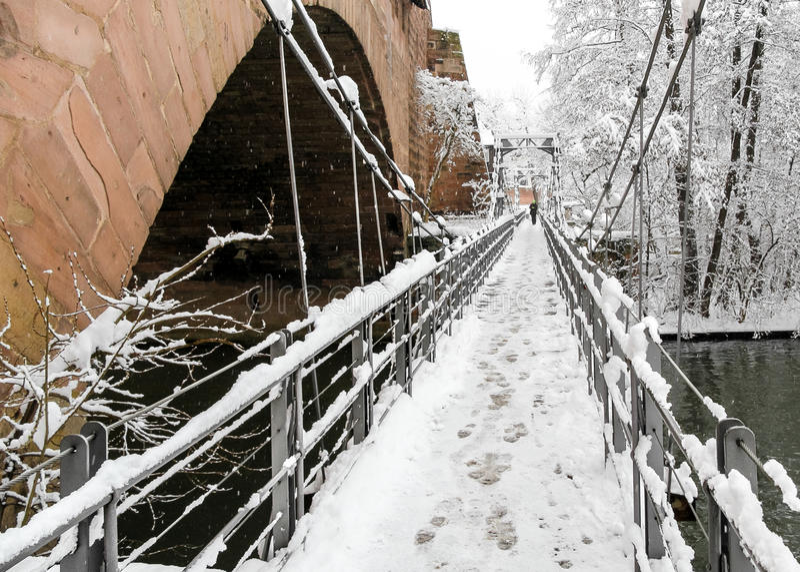 Snowy Nuremberg, Germany- iron bridge ( Kettensteg), old town city walls stock photography