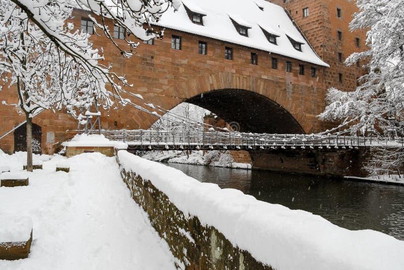 Snowy ponte del ferro di Norimberga, Germania (Kettensteg), vecchi mura di cinta della città immagini stock