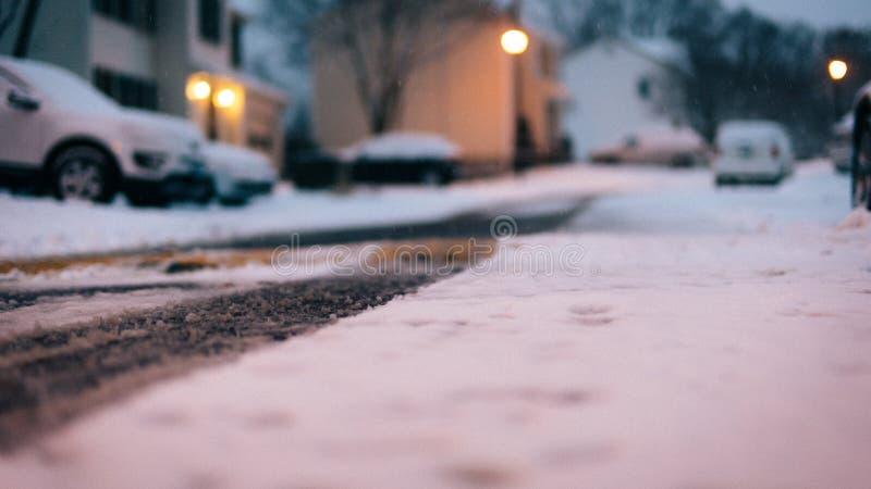 Snowy road close view asphalt winter. Snow road close view asphalt in the winter in the evening with street lamp lighting stock images