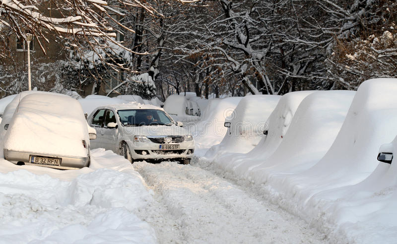 Snowy road and covered cars stock photos