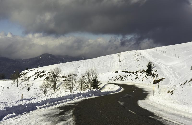 A snowy road curve in the mountains with a cloudy sky - horizontal stock photos
