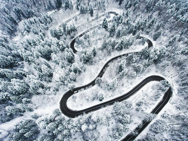 Snowy road in the forest. Extreme winding road high up in the mo. Untains. Aerial photography of a road in wintertime trough a forest covered in snow. High royalty free stock image