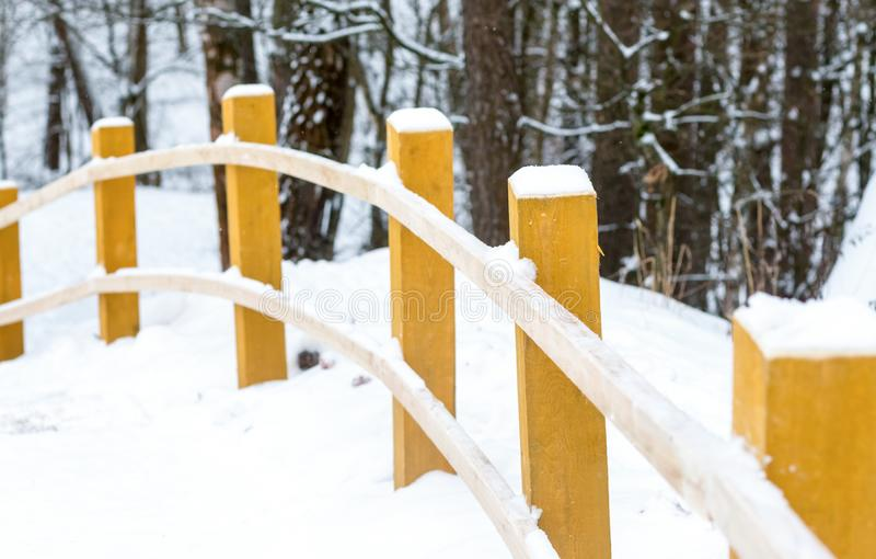 Snowy road forest walk yellow wooden pillars bent curtain railings stock photos