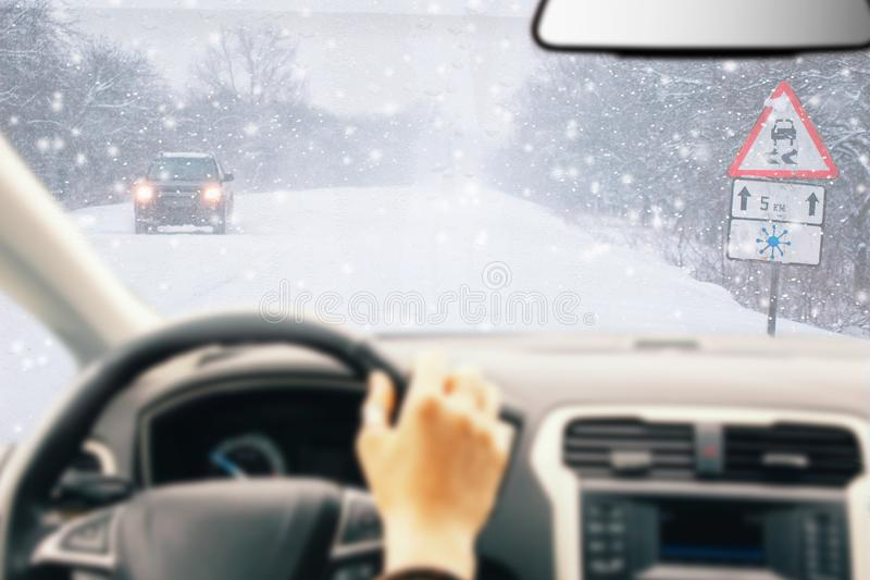 Snowy road with traffic sign Sudden and heavy snowfall on a country road. Driving on it becomes dangerous. Driver. Snowy road with traffic sign Sudden and heavy royalty free stock photo