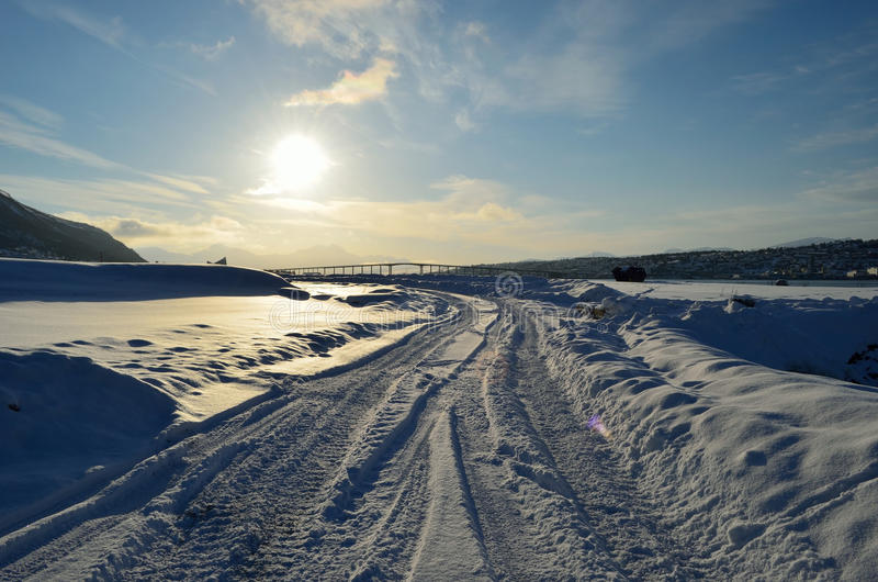 Snowy road with tromsoe city island in the background at sunrise. With blue sky stock photo