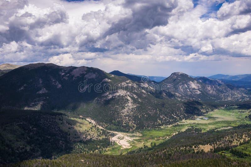 Snowy si rannuvola una valle verde in Rocky Mountains immagine stock