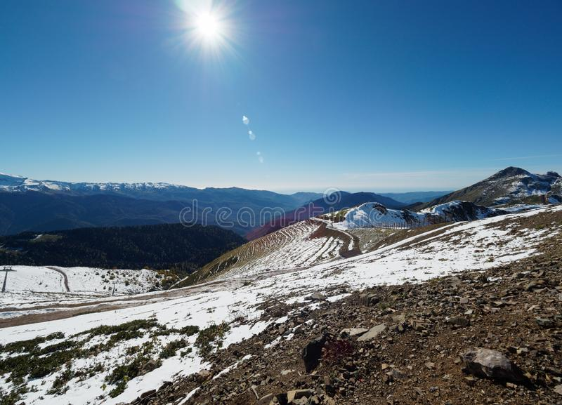 Snowy slope high mountains with ski lift. Blue sunny skies royalty free stock photo