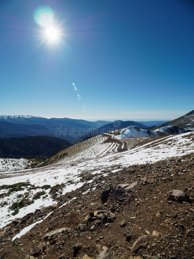 Snowy slope high mountains with ski lift. Blue sunny skies. Snow slope of a high mountain with a cable lift. Blue sunny sky royalty free stock photos