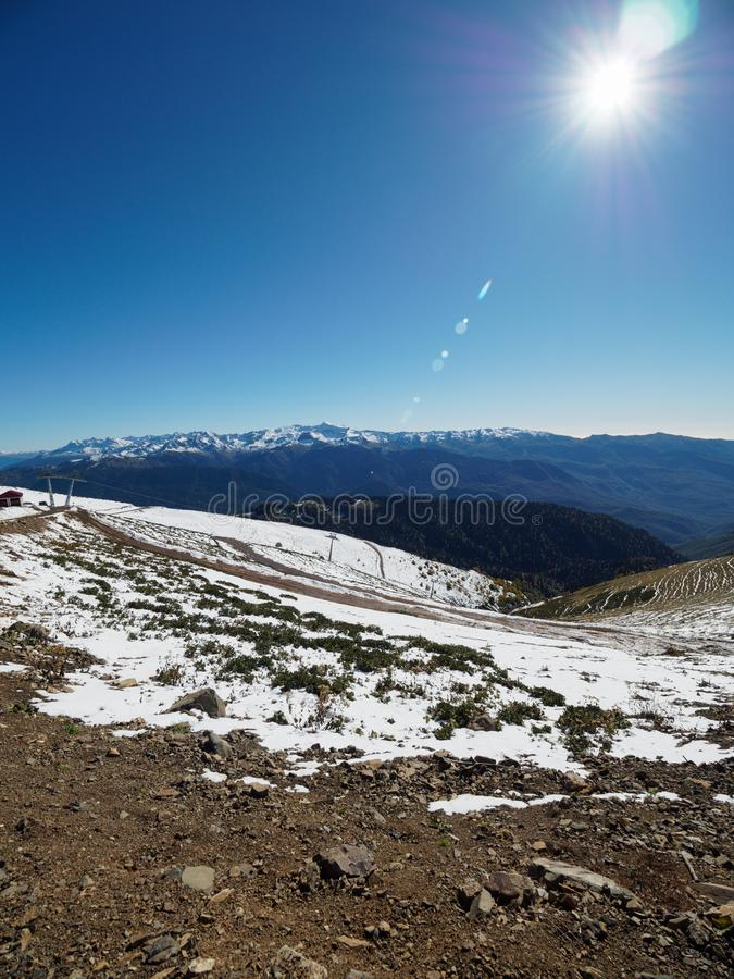 Snowy slope high mountains with ski lift. Blue sunny skies. Snow slope of a high mountain with a cable lift. Blue sunny sky royalty free stock images