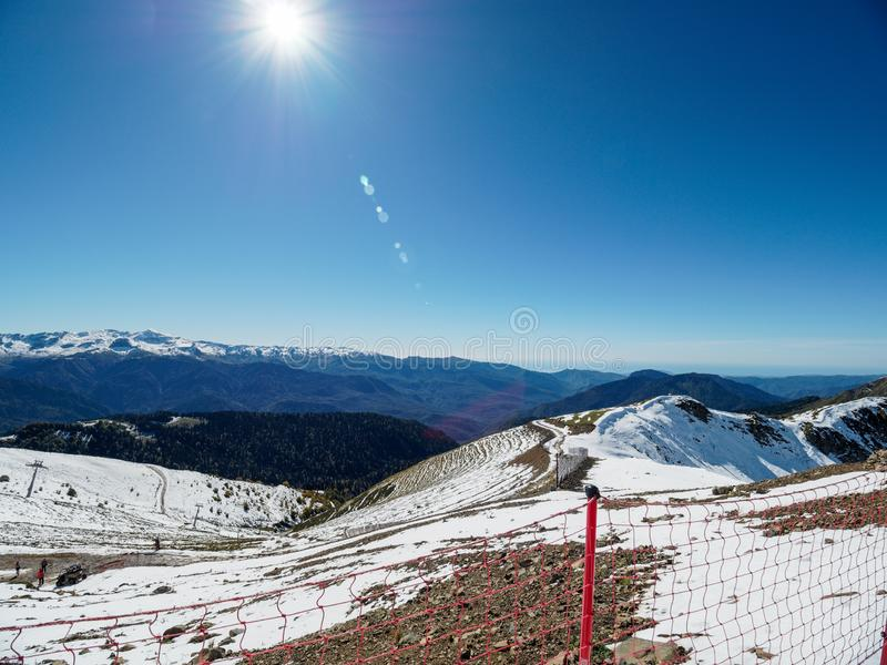 Snowy slope high mountains with ski lift. Blue sunny skies. Snow slope of a high mountain with a cable lift. Blue sunny sky royalty free stock image