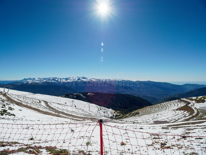 Snowy slope high mountains with ski lift. Blue sunny skies royalty free stock photos