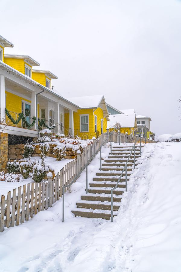 Snowy stairs along wooden fence of homes in Utah. Outdoor stairs with handrails on a snow covered slope in winter. The steps is beside the wooden fence of a stock photo
