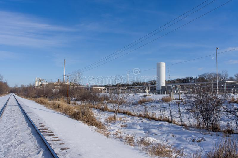 Snowy straight railroad track - industrial business with equipment off the tracks -  near the Minnesota River and near coal power. Plant royalty free stock photography
