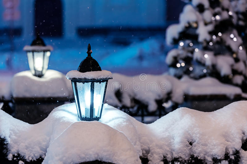 snowy street lamps in night city with fir-tree and christmas lights in background royalty free stock images