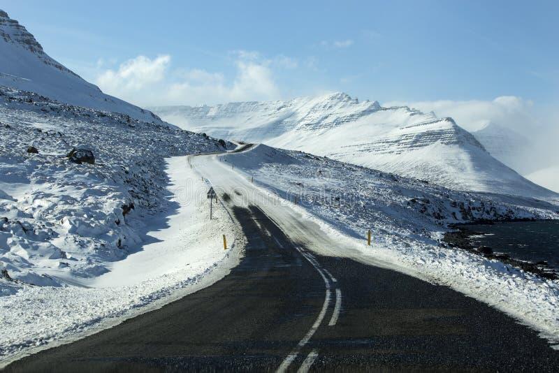 Snowy und vereiste Straße mit Vulkanbergen in der Winterzeit lizenzfreies stockfoto