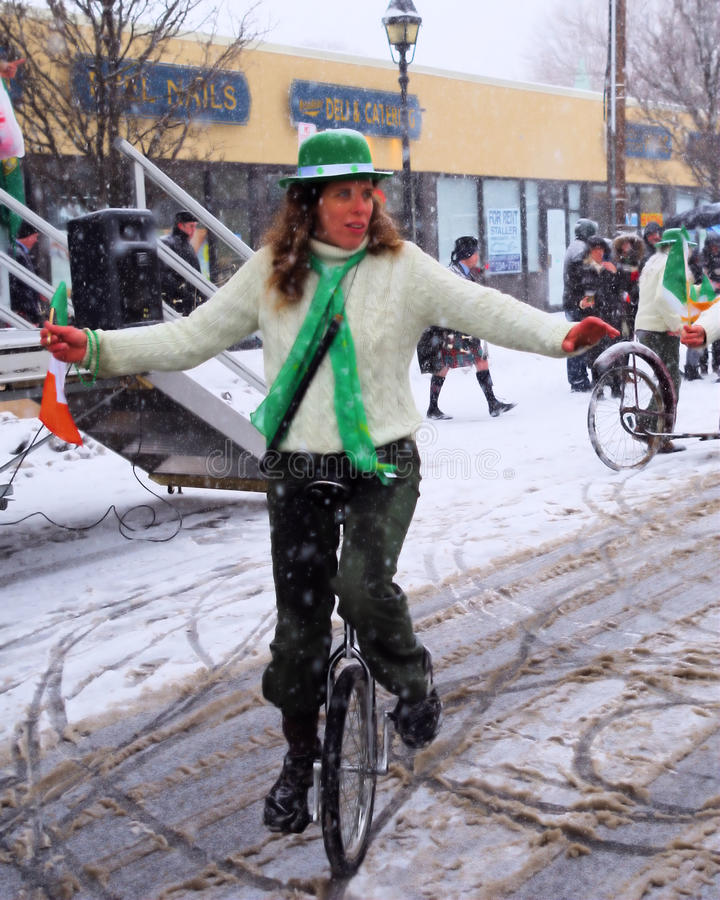 Snowy Unicycle. Uni-cyclist playing tunes on a flute at the early St. Patrick's Day Parade in Bethpage, Long Island, New York royalty free stock photo