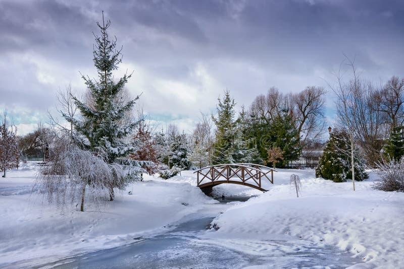 Snowy wenig Brücke über Teich stockfotografie