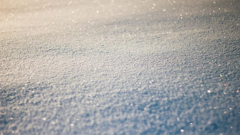Snowy white background. The texture of the snow. Shiny snow with bokeh and blurred background close-up. White snow-covered field. royalty free stock image
