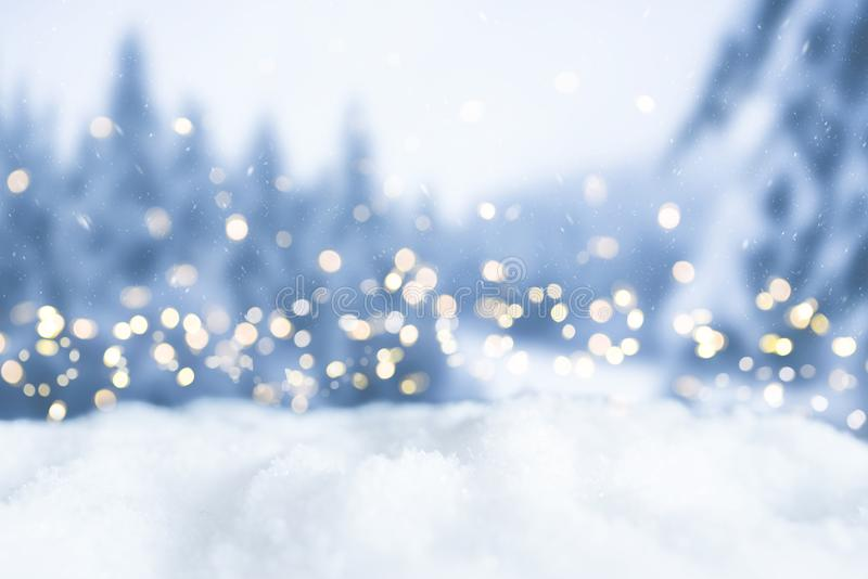 Snowy winter christmas bokeh background with lights and trees royalty free stock photo