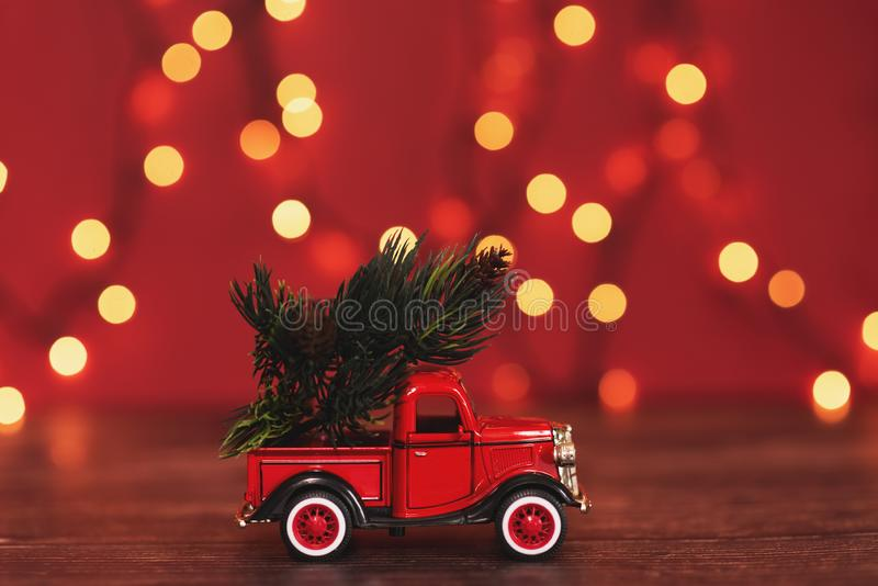 Snowy Winter Forest with miniature red car carrying a christmas tree and presents royalty free stock photos