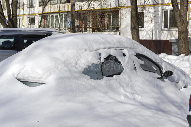 Snow covered the cars parked near the house. royalty free stock photo