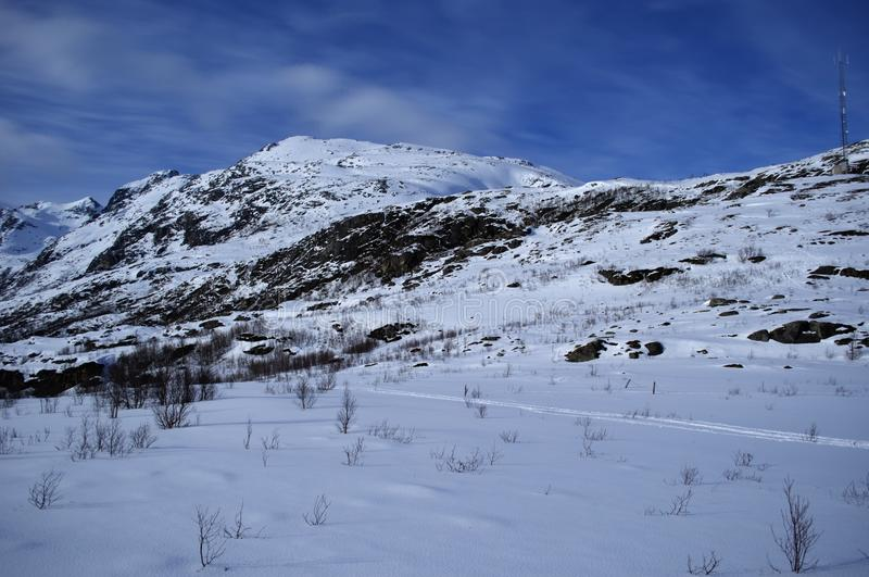 Snowy winter mountain in northern norway with deep blue sky backdrop royalty free stock photo