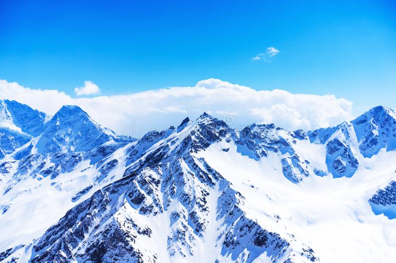 Snowy winter mountains and clear blue sky and clouds on a sunny day. Caucasus Mountains, Russia, view from the ski resort of Elbru. S royalty free stock images