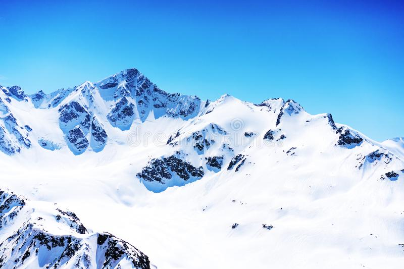 Snowy winter mountains and clear blue sky on a sunny day. Caucasus Mountains, Russia, view from the ski resort of Elbrus royalty free stock image