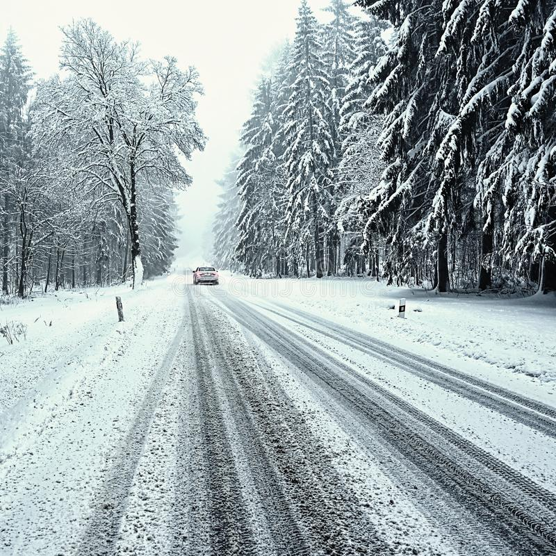 Snowy winter road with car. Dangerous car driving in the mountains in the winter. Concept for transportation, cars and travel royalty free stock photos