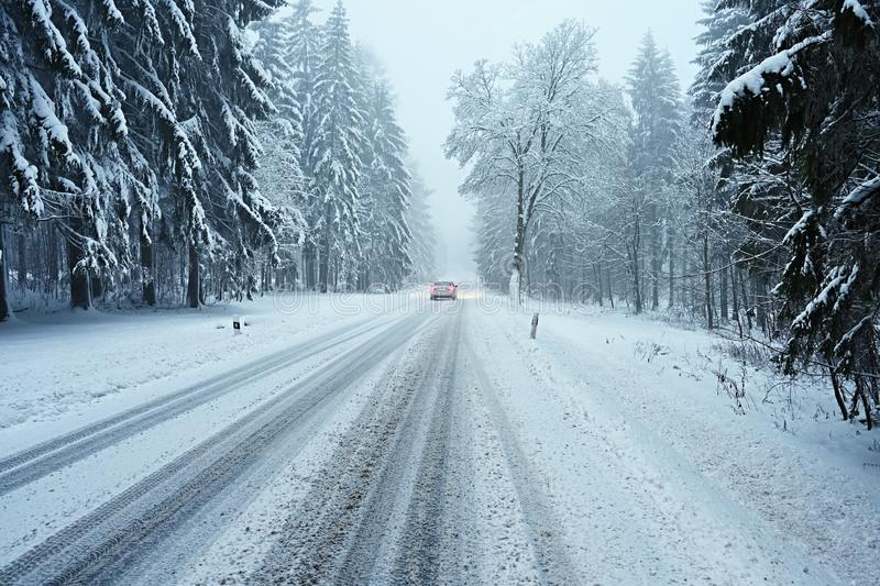 Snowy winter road with car. Dangerous car driving in the mountains in the winter. Concept for transportation, cars and travel.  stock image