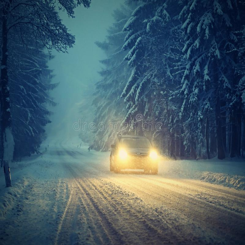 Snowy winter road with car. Dangerous car driving in the mountains in the winter. Concept for transportation, cars and travel.  royalty free stock images