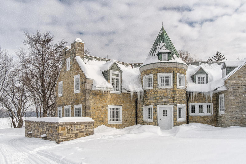 Snowy Winter scene stone house. Snowy Winter scene bushes, houses with trees on a snowyn day royalty free stock photos