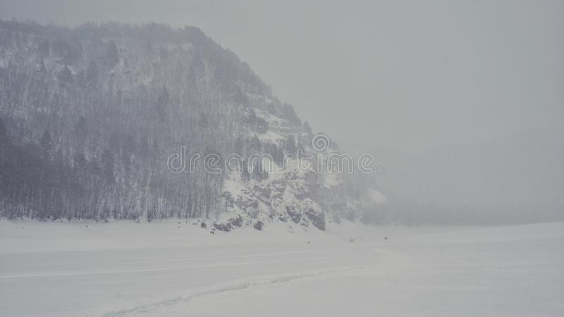 Snowy winter in the Urals. Mountain, nature, season, landscape, river, ice, trees, forest, flog stock photos