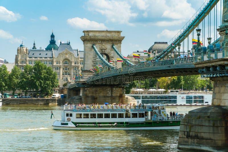 Snubbla fartyget som navigerar Donau nära Szechenyi den chain bron i Budap royaltyfri fotografi
