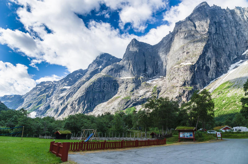 Snug camping near high rocks with playground. Cosy camping area with parking and playground surrunded by high mountains of Troll Wall, Norway royalty free stock photos