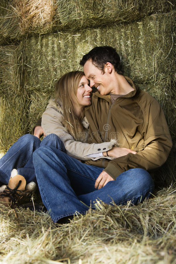 Snuggling couple. Mid-adult Caucasian couple snuggling in hay royalty free stock photo