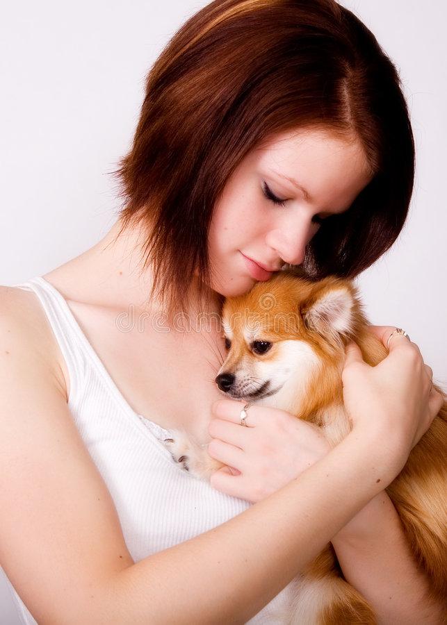 Snuggling with Puppy. Close up of a teen girl snuggling with her Pomeranian puppy royalty free stock photo