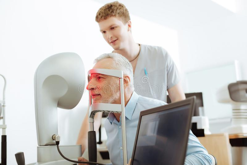 Snygg åldrig man som ler, medan lyssna till ögondoktorn royaltyfri foto
