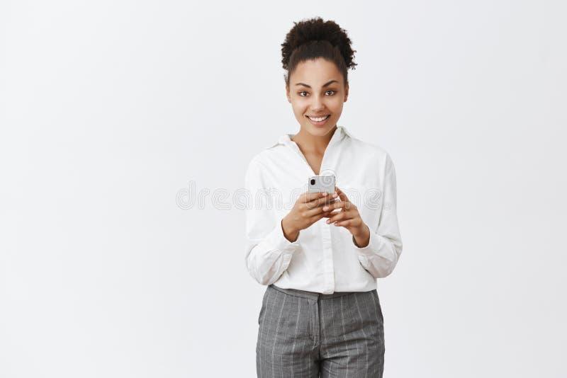 Snygg affärskvinna med mörk hud i dräkten som rymmer smartphonen och stirrar på kameran med det breda leendet som talar royaltyfri foto