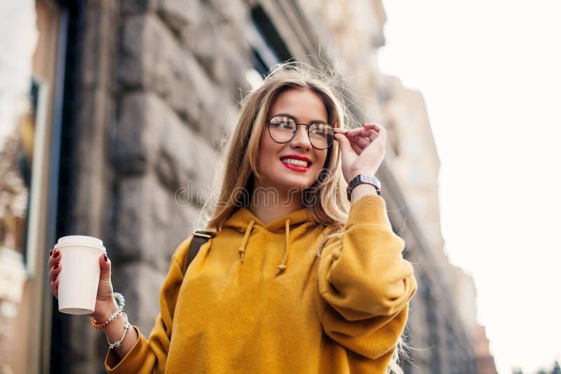 Snygg blond flicka med långt hår, medan gå ner den utomhus- ståenden för gata av den blonda unga kvinnan i ljus sweatsh royaltyfri foto