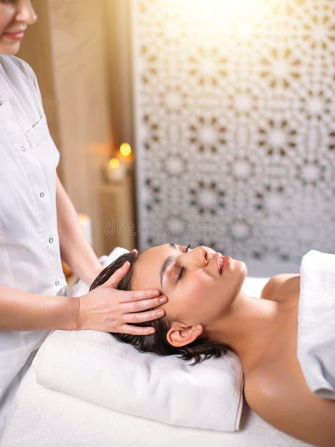 Snygg flicka med stängda ögon som får den head massagen i brunnsortsalongen arkivbilder