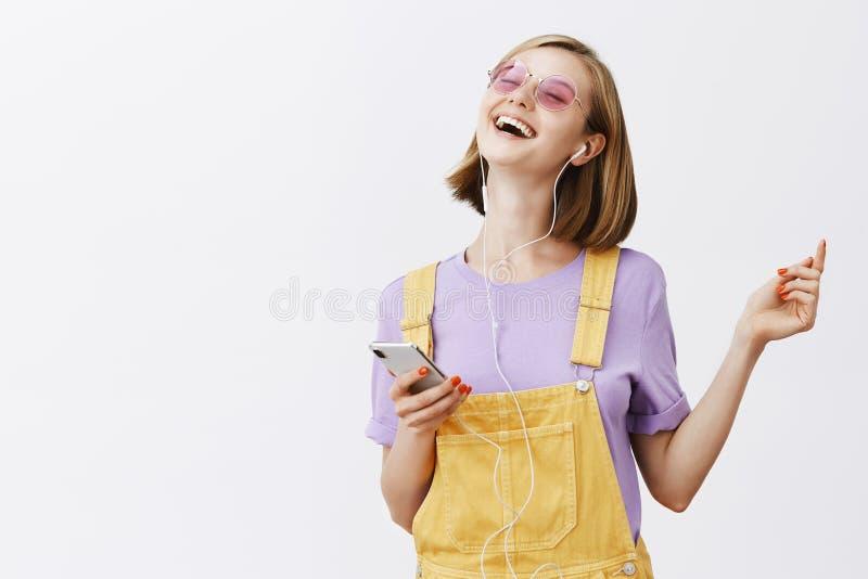 Snygg glad kvinna i stilfulla gula grova bomullstwillar över den purpurfärgade t-skjortan och solglasögon som dansar med stängda  royaltyfri foto