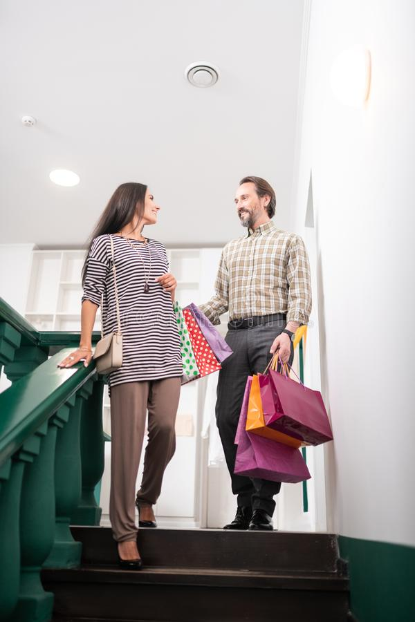 Snygg man som hjälper denhaired förtrollande charmiga kvinnan med shoppingpackar royaltyfri fotografi