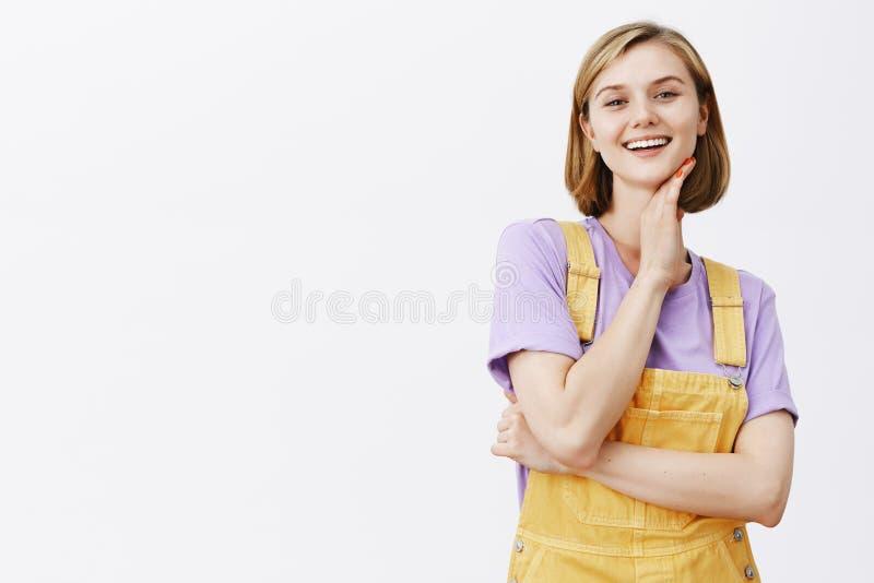 Snygg nöjd säker kvinna med blond kort frisyr, den rörande halsen försiktigt och le med stolt och själv royaltyfri foto