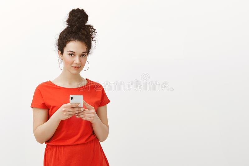 Snygg stilfull kvinnlig flicka med lockigt hår som kammas i bulle, i röd klänning, hållande smartphone och att stirra på kameran arkivbild
