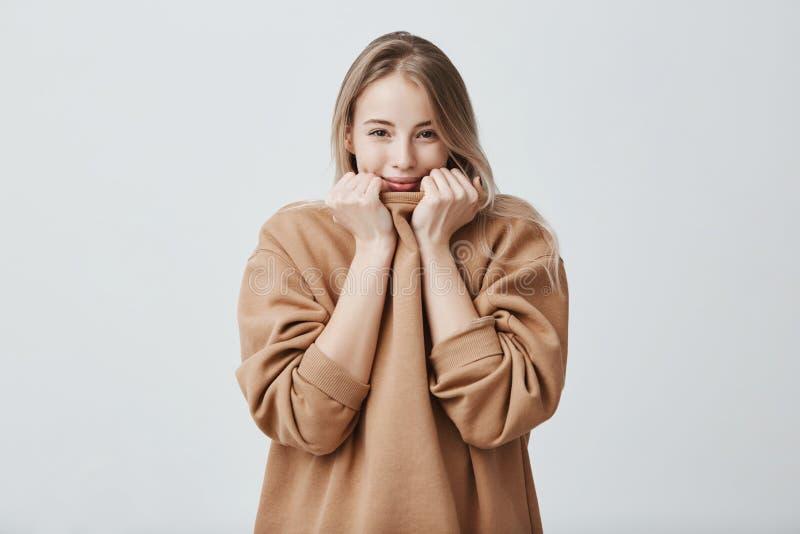 Snyggt härligt le för flicka som behas för att höra komplimang som isoleras mot grå studiobakgrund Nätt kvinnligt arkivfoton