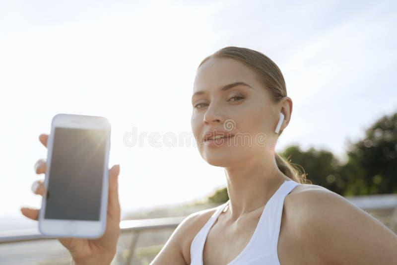 Snyggt leende idrottslig dam som visar mobiltelefon royaltyfri fotografi